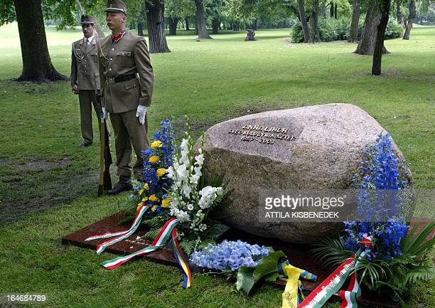 Members of the honour guard stand on guard at the 'Memorial stone' of former Swedish Foreign Minister Anna Lindh in the most famous public park of...