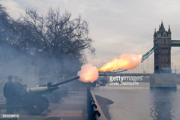Members of the Honourable Artillery Company fire a 62 round royal gun salute from the Gun Wharf outside the Tower of London with Tower Bridge seen in...