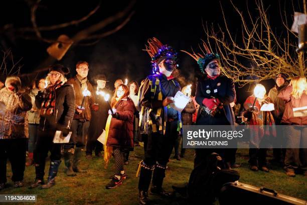 Members of the Hook Eagle Morris Men stand alongside villagers as they sing to the apple trees in the orchard during the annual Wassail night in...