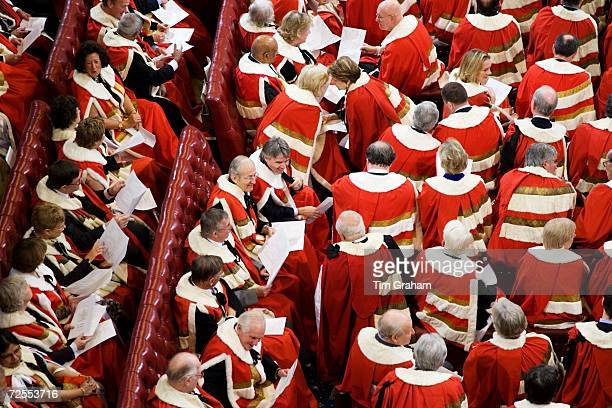 Members of the House of Lords wearing ceremonial red robes trimmed with white fur in the House of Lords for the State Opening of Parliament November...