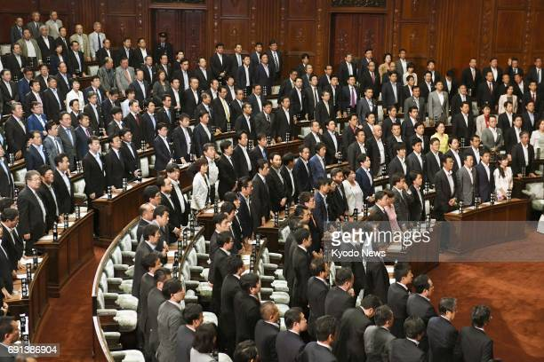 Members of the House of Representatives stand during a plenary session in Tokyo on June 2 to show their approval of a bill enabling Emperor Akihito...