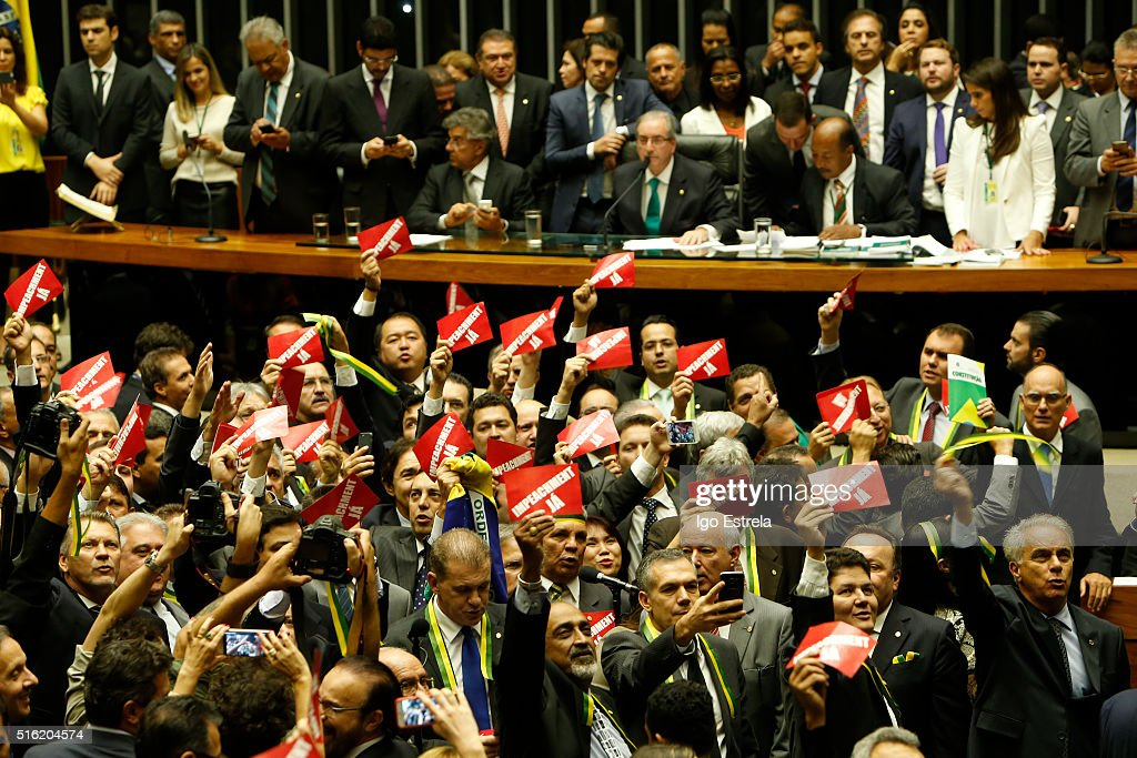 Members of the house who oppose the government hold signs that read 'Impeachment Now' while Eduardo Cunha, Speaker of the house, addresses the plenary during a special session of legislators negotiating the nomination of memberson of the committee that will initiate the impeachment process of President DIlma Rousseff on March 17, 2016 in Brasilia, Brazil. His controversial cabinet appointment comes in the wake of a massive corruption scandal and economic recession in Brazil.