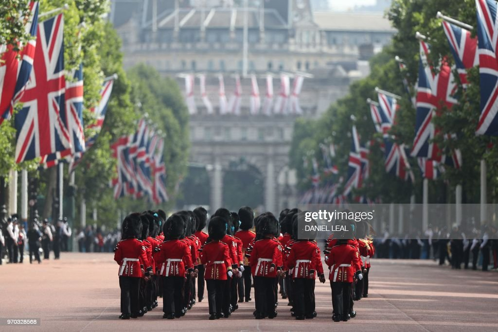 TOPSHOT - Members of the Household Division, march down The Mall to Horseguards parade ahead of the Queen's Birthday Parade, 'Trooping the Colour', in London on June 9, 2018. - The ceremony of Trooping the Colour is believed to have first been performed during the reign of King Charles II. In 1748, it was decided that the parade would be used to mark the official birthday of the Sovereign. More than 600 guardsmen and cavalry make up the parade, a celebration of the Sovereign's official birthday, although the Queen's actual birthday is on 21 April.