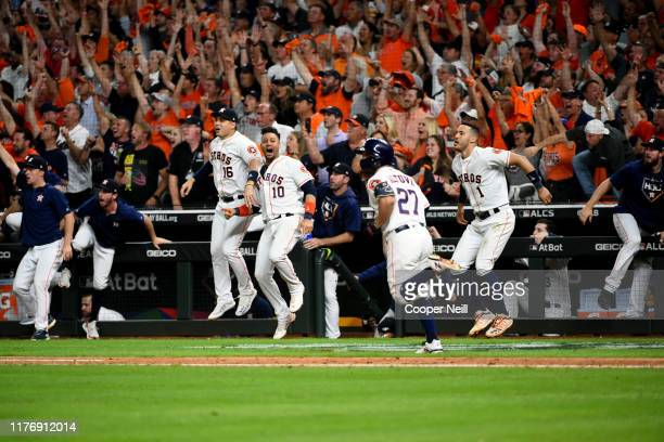 Members of the Houston Astros begin to celebrate the walk-off two-run home run by Jose Altuve in the bottom of the ninth inning to win Game 6 of the...
