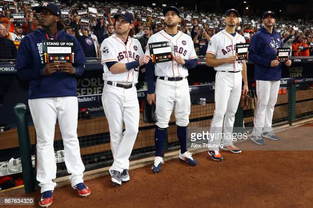 Members of the Houston Astros stand outside the dugout holding Stand Up 2 Cancer placards during Game 4 of the 2017 World Series against the Los...