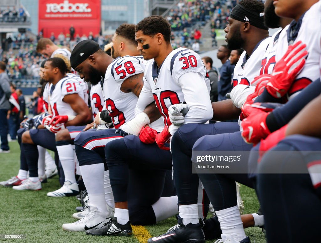 Members of the Houston Texans, including Kevin Johnson #30 and Lamarr Houston #58, kneel during the national anthem before the game at CenturyLink Field on October 29, 2017 in Seattle, Washington. During a meeting of NFL owners earlier in October, Houston Texans owner Bob McNair said 'we can't have the inmates running the prison,' referring to player demonstrations during the national anthem.