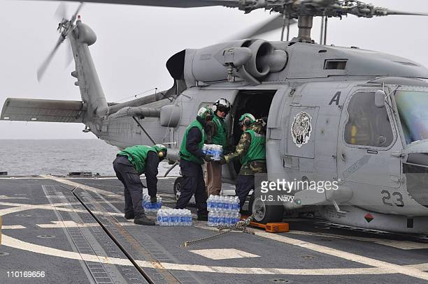 Members of the HSL43 air detachment embarked on board USS Preble load cases of bottled water to take to earthquake and tsunami survivors in Japan on...