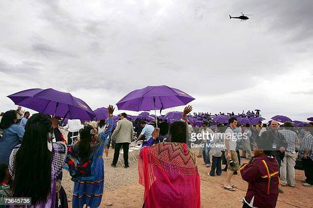 Members of the Hualapai tribe hold promotional umbrellas and wave to a helicopter filming them for a promotional shoot following the first official...