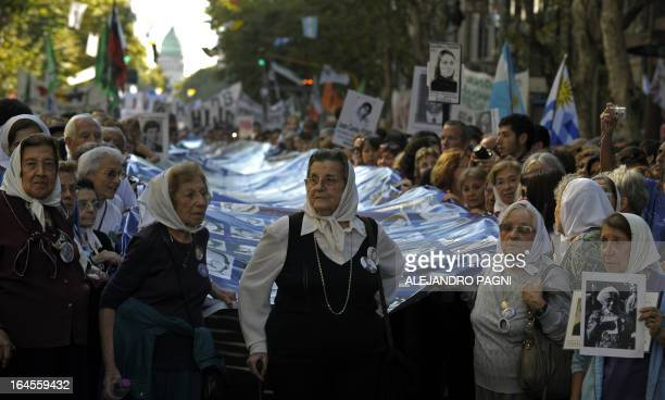 Members of the Human Rights organization Madres de Plaza de Mayo Linea Fundadora and other demonstrators carry a large banner with the portraits of...