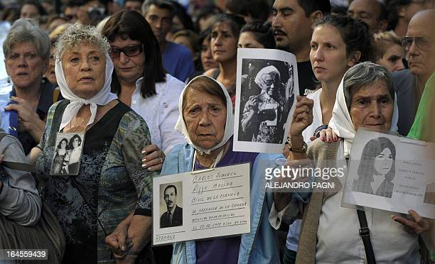 Members of the Human Rights organization Madres de Plaza de Mayo Linea Fundadora and other demonstrators hold portraits of people who went missing in...