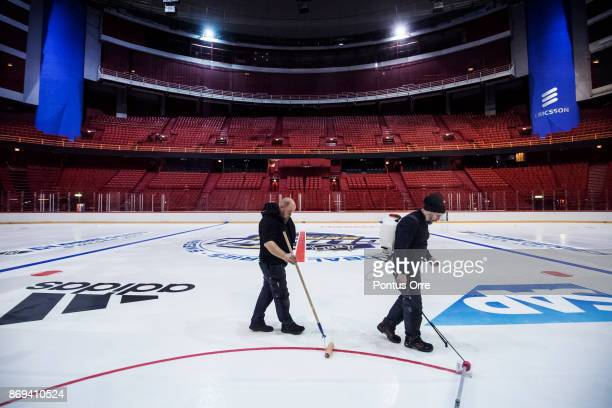Members of the ice crew install logos and lines on the ice during the rink build out ahead of the SAP NHL Global Series between Ottawa Senators and...
