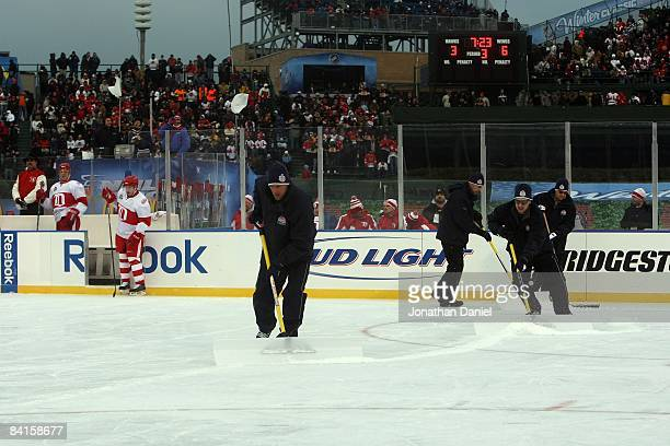 Members of the ice crew shovel lose ice from the rink during the NHL Winter Classic between the Chicago Blackhawks and the Detroit Red Wings at...