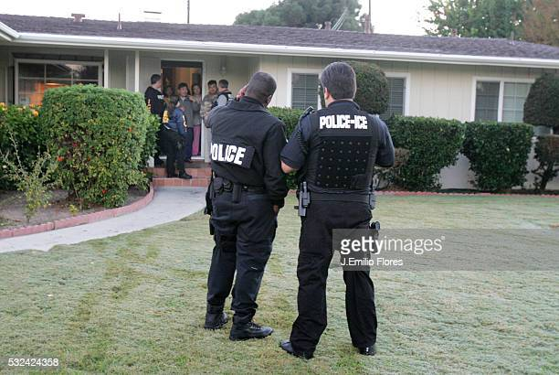 Members of the immigrant removal task force of the Immigration and Customs Enforcement outside a home during an early morning raid to arrest and...