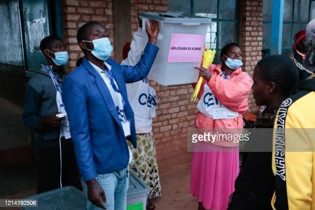 Members of the Independent National Electoral Commission show voters the empty ballot boxes before opening a polling station during the presidential...