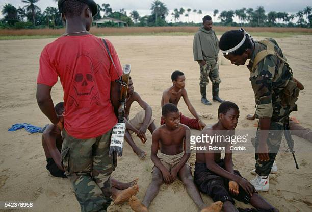 Members of the Independent National Patriotic Front of Liberia question a group of young civilians accused of collaborating with enemy forces...
