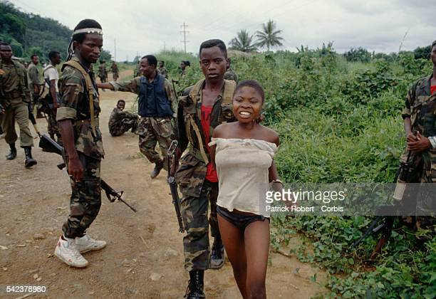 Members of the Independent National Patriotic Front of Liberia hold a civilian woman prisoner for giving food to enemy forces Responding to years of...