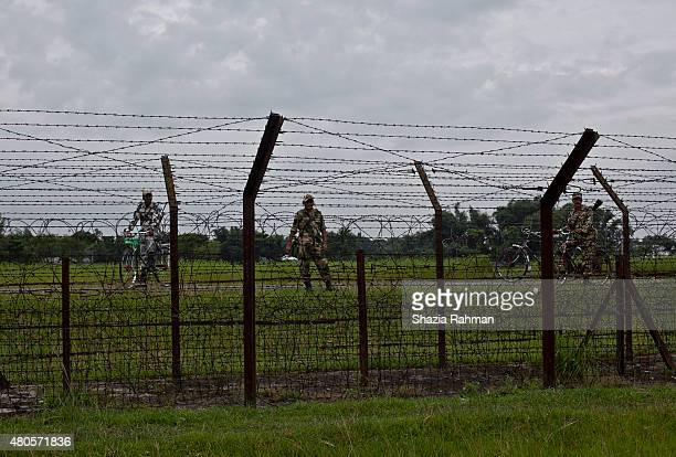 Members of the Indian BSF stand across from the India/Bangladesh border fence July 10 2015 in Lalmonirhat District Bangladesh The India Bangladesh...