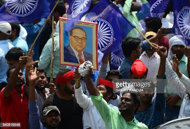 Members of the Indian Dalit community stage a protest with a portrait of 20th century social reformer B R Ambedkar during a countrywide strike...