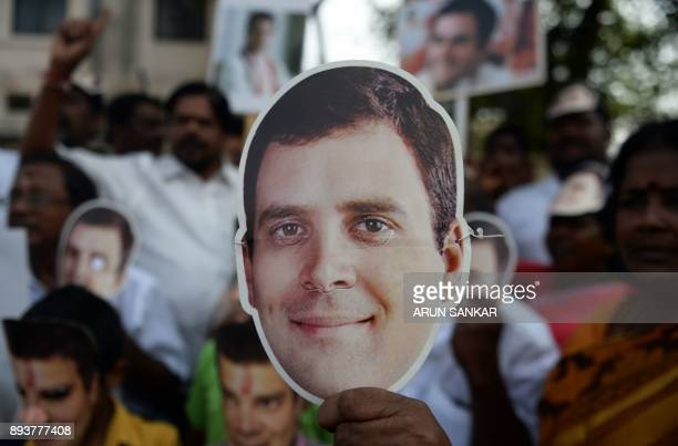 Members of the Indian National Congress party celebrate as they display masks of the newlyelected party President Rahul Gandhi in Chennai on December...