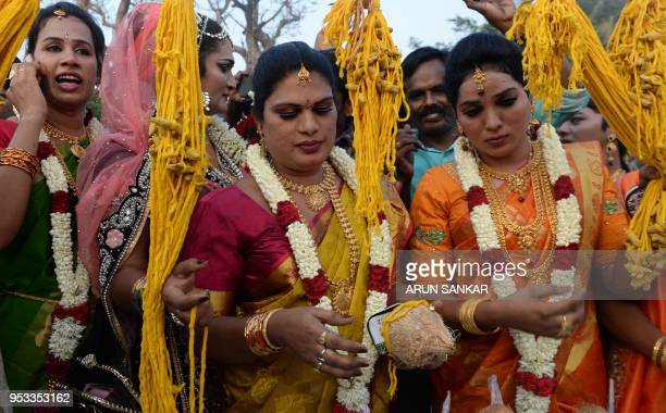 Members of the Indian transgender community dressed as brides purchase a 'thali' to be tied around their necks during a ritual signifying marriage to...