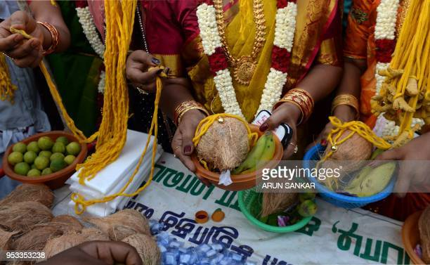 TOPSHOT Members of the Indian transgender community dressed as brides purchase a 'thali' to be tied around their necks during a ritual signifying...