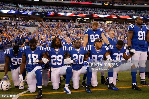 Members of the Indianapolis Colts stand and kneel for the national anthem prior to the start of the game between the Indianapolis Colts and the...