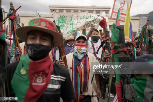 Members of the indigenous guard walk holding up their batons as they take part in a demonstration during a general strike against social and economic...