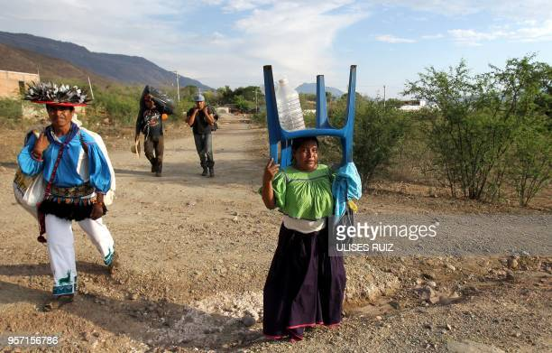 Members of the indigenous Wixaritari communities from Bolanos municipality walk back home after being on guard in a road blockade during a protest...