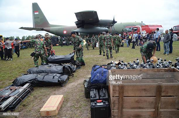 Members of the Indonesia marines unload their diving equipment as they arrive at Pangkalan Bun air base in Central Kalimantan on December 31 to join...