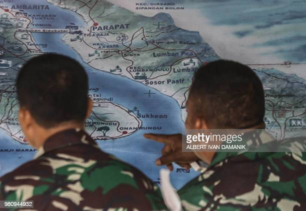 Members of the Indonesian rescue team look at a map as they prepare to deploy sonar equipment to help search for missing passengers at the Lake Toba...