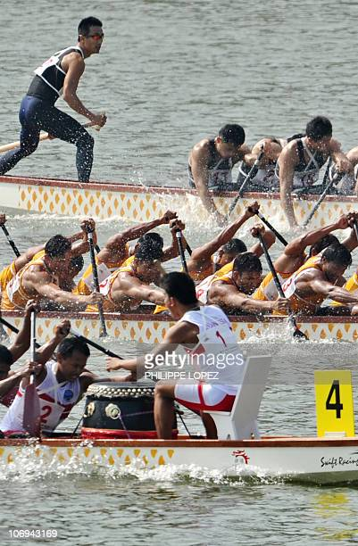 Members of the Indonesian team paddle against the Myanmar and Taiwan boats during the men's 1000m dragon boat straight race at the 16th Asian Games...