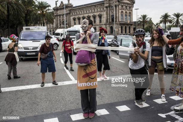 Members of the Insitut del Teatre and the CBD Poble Sec perform on a road as they take part in a demonstration and general strike in the Parallel...