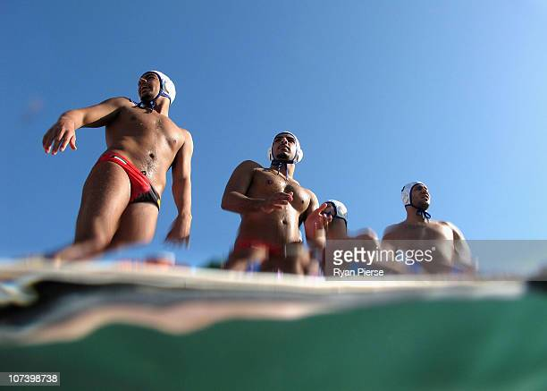 Members of the IOC Athletes from Kuwait team prepare to jump into the sea before the round robin match between Syria and IOC Athletes from Kuwait...