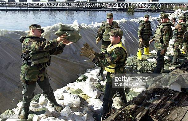 Members of the Iowa National Guard pass sandbags as they reinforce a levee protecting downtown Davenport, Iowa 25 April 2001. The Mississippi River...
