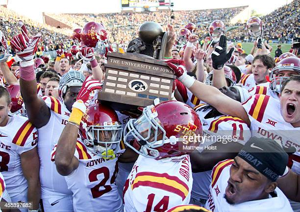 Members of the Iowa State Cyclones celebrate with the Cy-Hawk trophy after defeating the Iowa Hawkeyes 20-17, on September 13, 2014 at Kinnick...