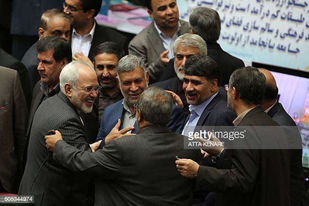 TOPSHOT Members of the Iranian parliament greet Iranian Foreign Minister Mohammad Javad Zarif after his return from Vienna ahead of presenting the...