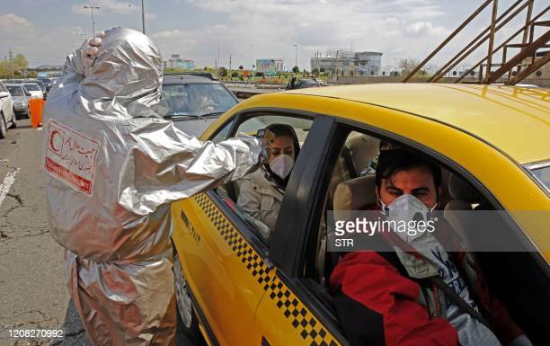 Members of the Iranian Red Crescent test people for coronavirus Covid-19 symptoms, as police blocked Tehran to Alborz highway to check every car...