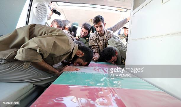 Members of the Iranian Revolutionary Guard mourn over the casket of Iran's Revolutionary Guards Brigadier General Mohsen Ghajarian who was killed in...