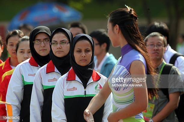 Members of the Iranian women's shooting team walk towards a Chinese hostess at the start of the medals ceremony of the women's 50m Rifle 3 Positions...