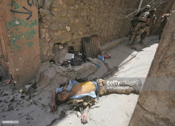 Members of the Iraqi antiterrorism forces walk past a body of a fighter in the Old City of Mosul on June 22 during the ongoing offensive by Iraqi...