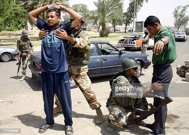 Members of the Iraqi Civil Defense Corps frisk two Iraqi men at a checkpoint outside Baghdad's Shiite neighborhood of Sadr City 15 May 2004 ICDC and...