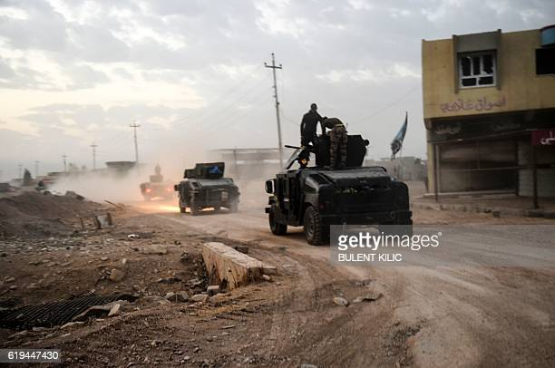 TOPSHOT Members of the Iraqi Counter Terrorism Service drive near the village of Bazwaya on the eastern edges of Mosul tightening the noose on Mosul...