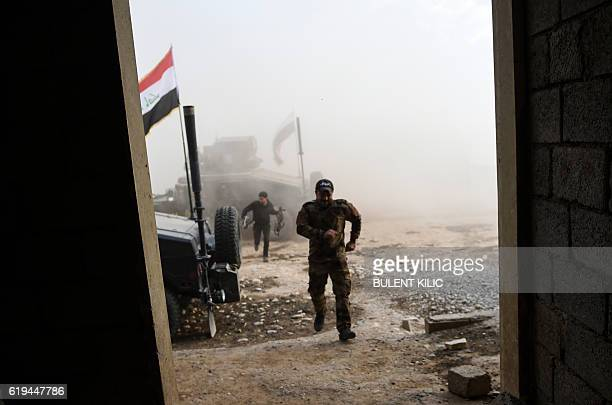 TOPSHOT Members of the Iraqi Counter Terrorism Service take shelter after a mortar shell hit nearby near the village of Bazwaya on the eastern edges...