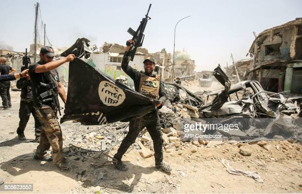 Members of the Iraqi Counter-Terrorism Service cheer as they carry upside-down a black flag of the Islamic State group, with the destroyed Al-Nuri...