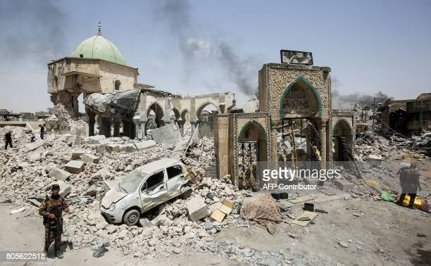 Members of the Iraqi Counter-Terrorism Service gather outside the destroyed gate of the Al-Nuri Mosque while others inspect the interiors, in the Old...