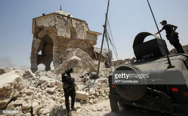 Members of the Iraqi CounterTerrorism Service gather outside the destroyed AlNuri Mosque in the Old City of Mosul on July 2 during the Iraqi...