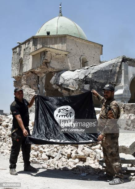 Members of the Iraqi CounterTerrorism Service hold upsidedown the black flag of the Islamic State group outside the destroyed AlNuri Mosque in the...
