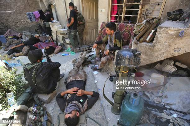 Members of the Iraqi CounterTerrorism Service rest while advancing towards the Grand Mosque of Nuri in the Old City of Mosul on June 29 during the...