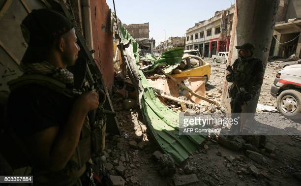 Members of the Iraqi CounterTerrorism Service take cover while advancing towards the Grand Mosque of Nuri in the Old City of Mosul on June 29 during...