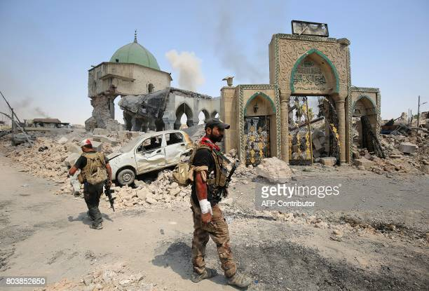 Members of the Iraqi CounterTerrorism Service walk past the destroyed AlNuri Mosque in the Old City of Mosul as they continue their offensive to...